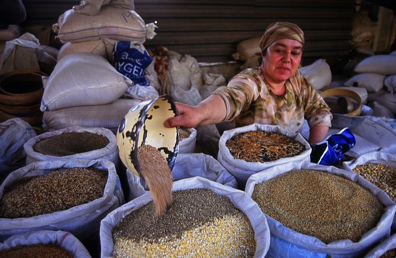 A vendor measures out grains for sale at the market. Photo credit: Peter Guttman