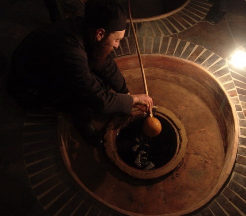 A winemaker checks on his product, which ages to perfection in an underground qvevri. Photo credit: John Wurdeman