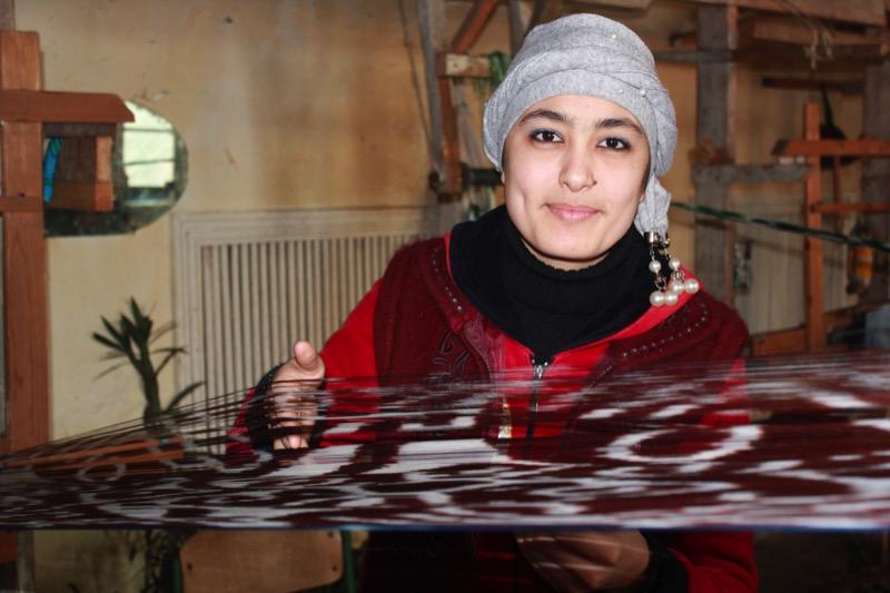 A weaver in Fergana demonstrates the time-consuming process of making silk fabrics by hand. Photo credit: Marina Karptsova