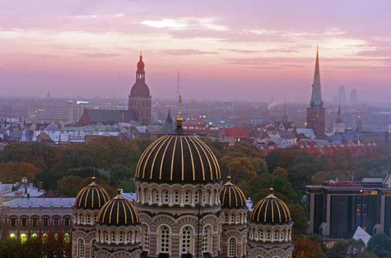 The sun sets over the rooftops of Riga, Latvia. Photo credit: Peter Guttman