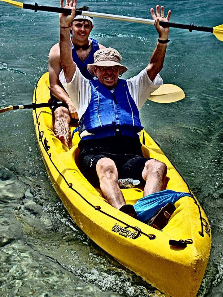 Grandfather jubilantly sea-kayaks with his grandson in Croatia on a custom journey. Photo credit: Iris Adventures