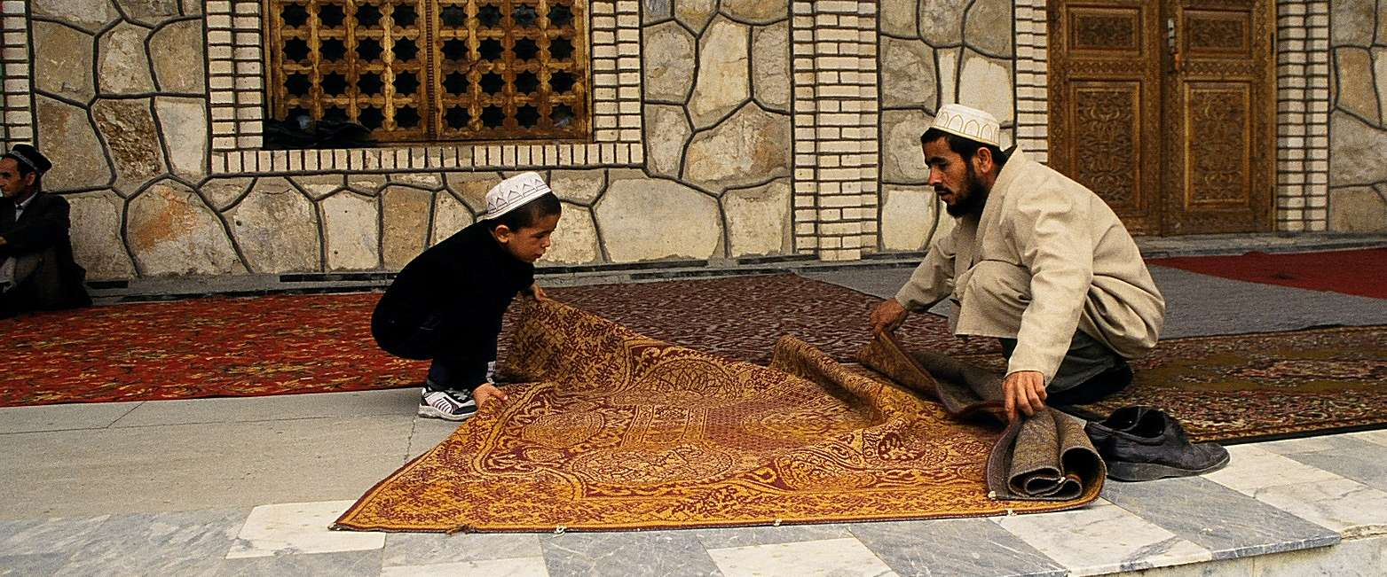 Father and son roll up rugs in Tajikistan. Photo credit: Michel Behar