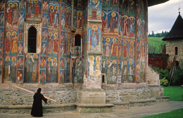 A nun taps a mallet against a wooden semantron, calling faithful to prayer in Bucovina, Romania. Photo credit: Peter Guttman