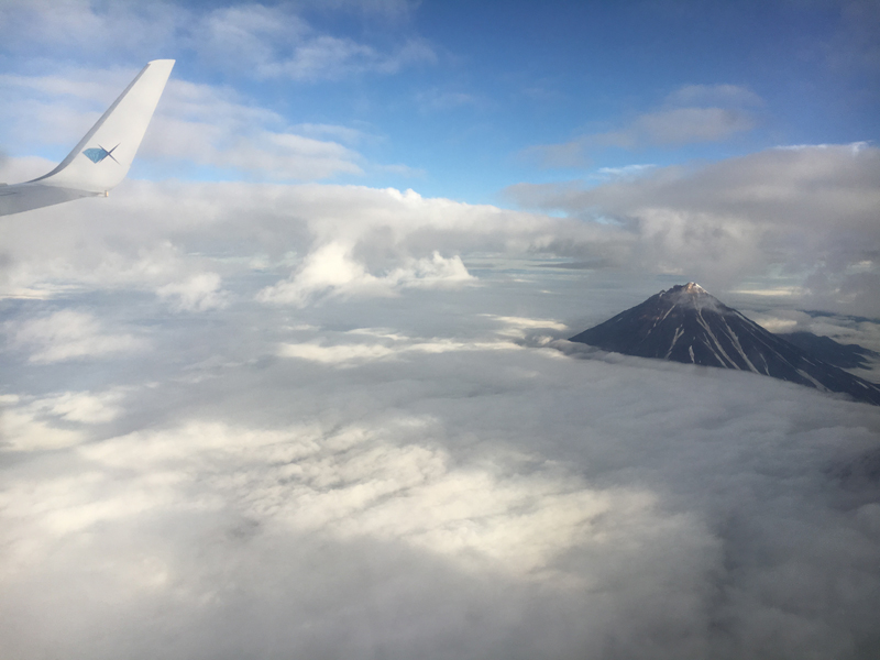 A volcano peeks through the clouds on our descent into Kamchatka. Photo credit: Jake Smith