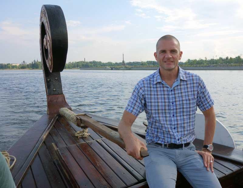 John steers the boat on the Volga River