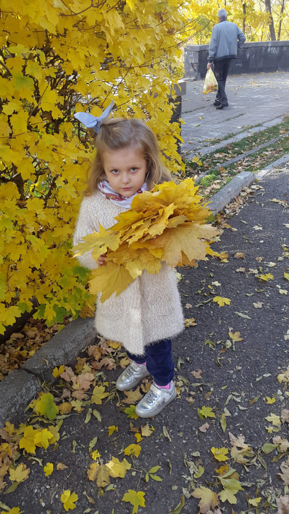 A Yerevan girl collects handfuls of fall foliage. Photo credit: Anya von Bremzen
