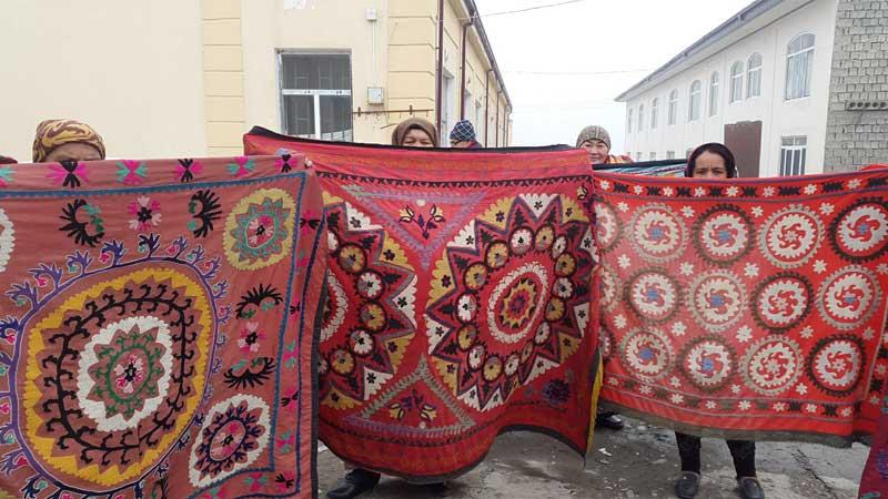 Suzani vendors display their handiwork at a local market. Photo credit: Anya von Bremzen