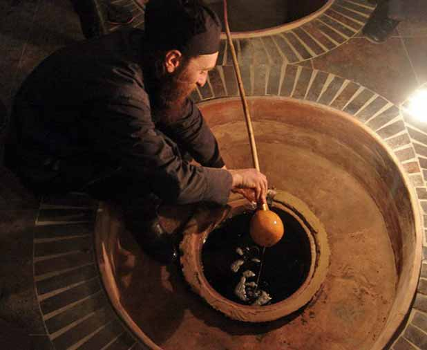 A Georgian winemaker dips into a qvevri, demonstrating a UNESCO-listed ancient method of making wine. Photo credit: John Wurdeman
