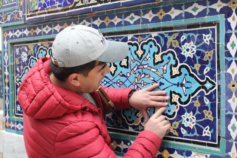 MIR Tour Manager Abdu Samadov explains the significance of the patterns in Silk Road tile work. Photo credit: Tia Low