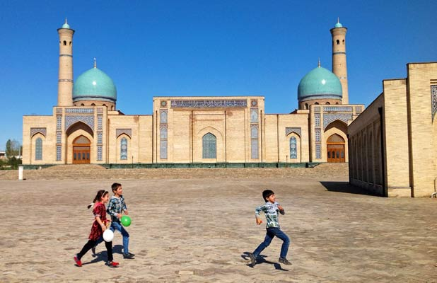 A mix of old and new, as young kids play outside Tillya Sheikh Mosque in Tashkent. Photo credit: Michel Behar