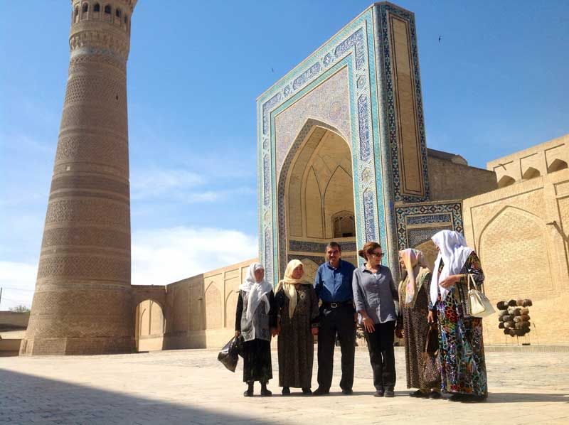 Patricia Schultz, author of 1,000 Places to See Before You Die, traveled with MIR in 2014; here she's pictured with a group of locals in Uzbekistan. Photo credit: Michel Behar