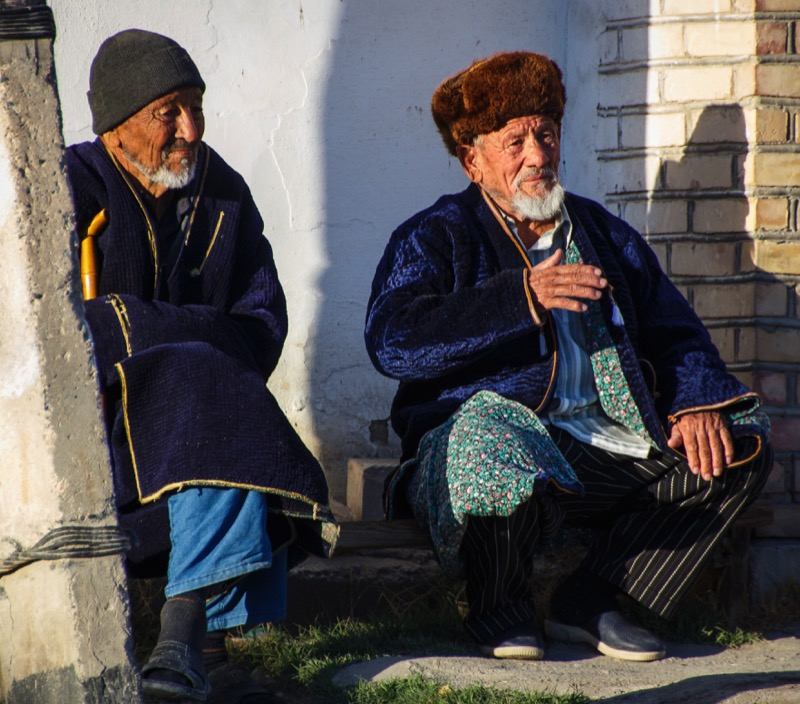 Two friends, wearing the traditional men's chapan enjoy a quiet moment in Bukhara. Photo credit: Lindsay Fincher