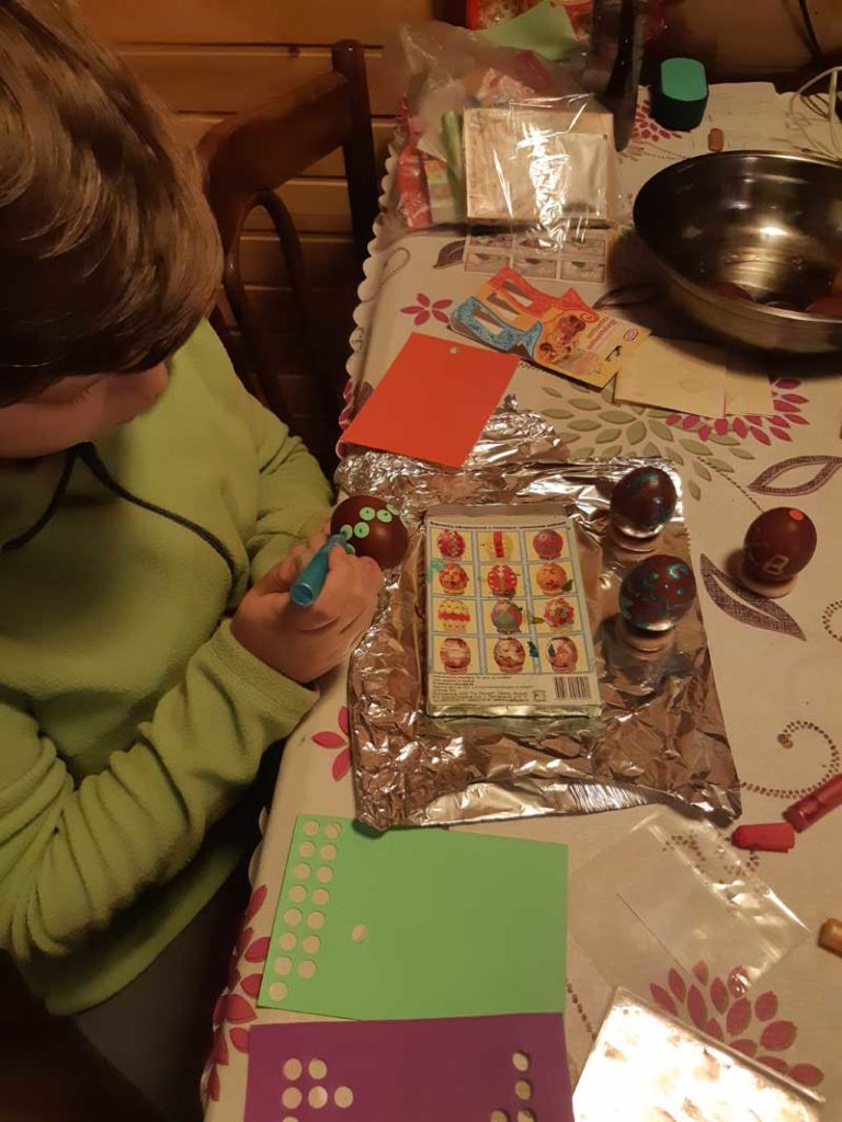 Olga's son enjoys the craft of decorating eggs at the dacha.