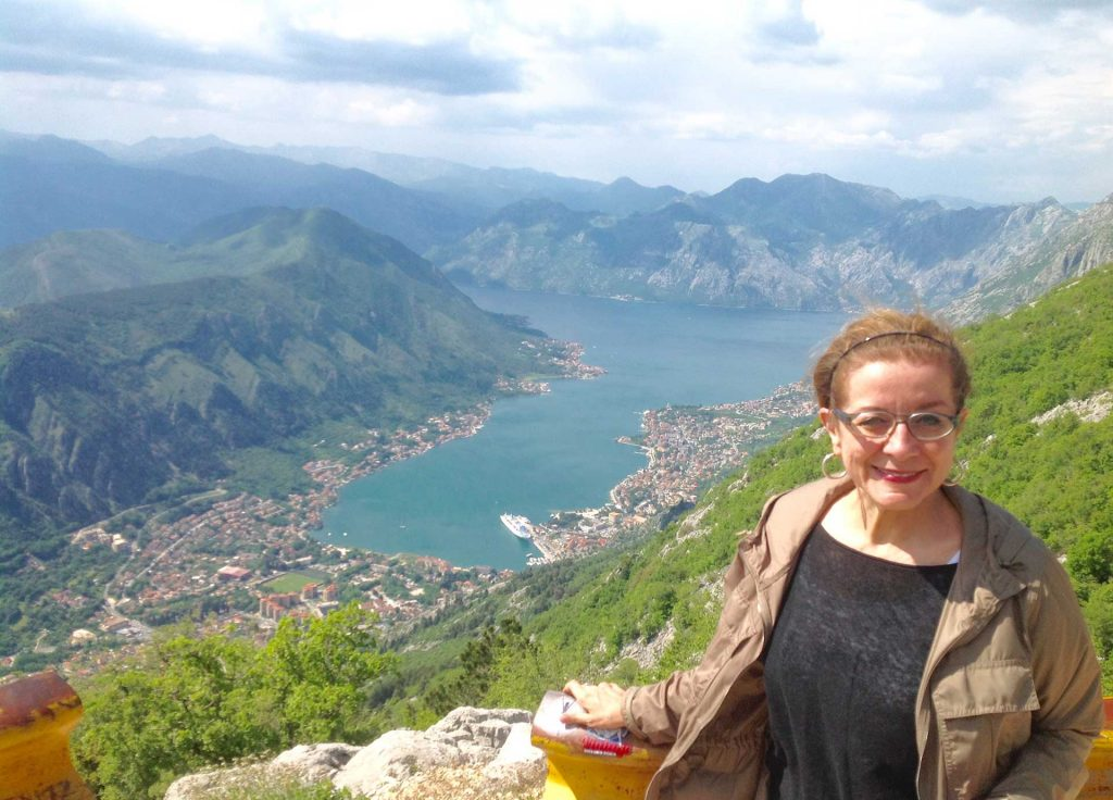 """Patricia Schultz, author of """"1,000 Places to See Before You Die"""", traveled to the Balkans with MIR; here she's pictured in Montenegro, overlooking the Bay of Kotor. Photo credit: Michel Behar"""