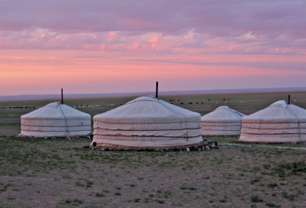 Mongolian steppe at sunset, with gers dotting the landscape. Photo credit: Andrew Barron