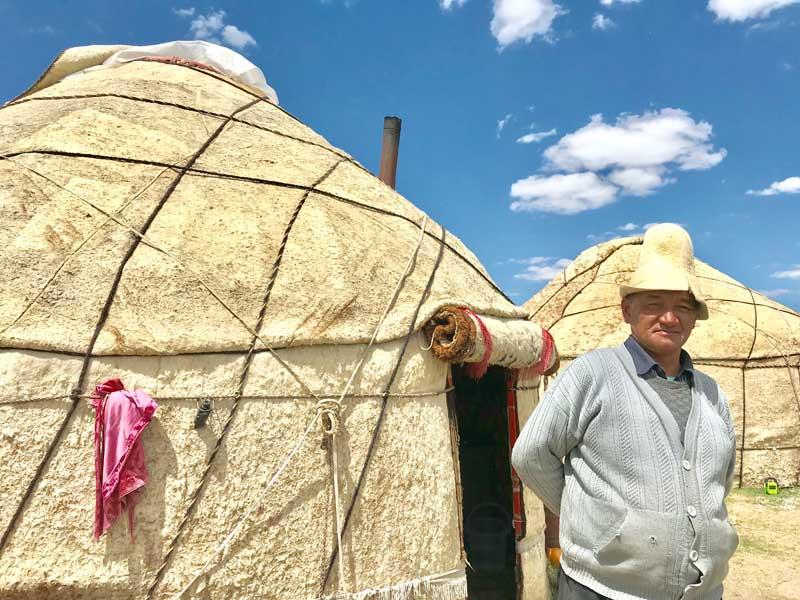 A Kyrgyz man stands outside of his yurt, wearing a kalpak. Photo credit: Michel Behar