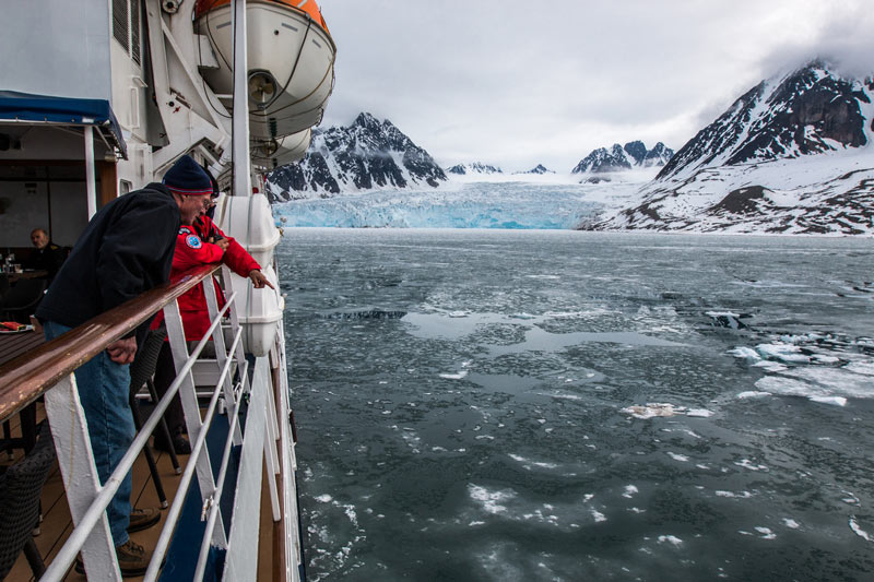 Spotting sea life from the deck, with a blue glacier backdrop. Photo credit: Jonathan Zaccaria