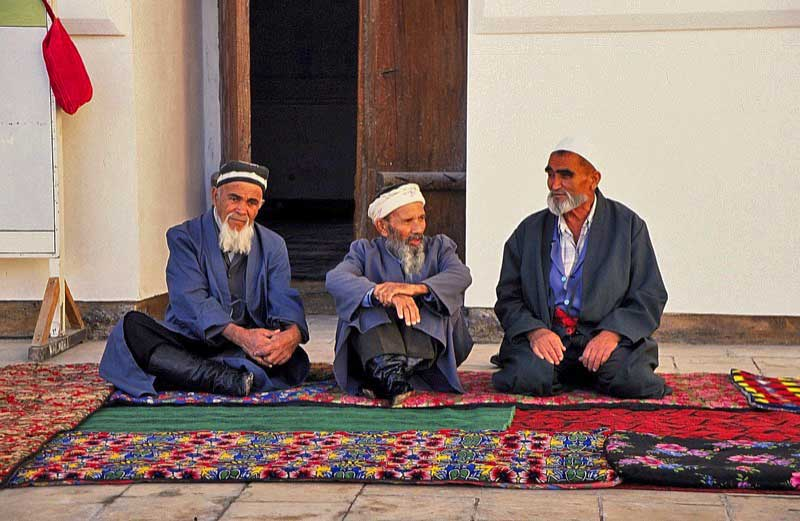 Older Bukharans converse in typical Uzbek style: often cross-legged, seated on Central Asian carpets. Photo credit: Michel Behar