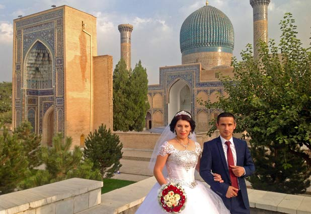 Newlyweds pause for pictures among Samarkand's ancient architecture. Photo credit: Michel Behar